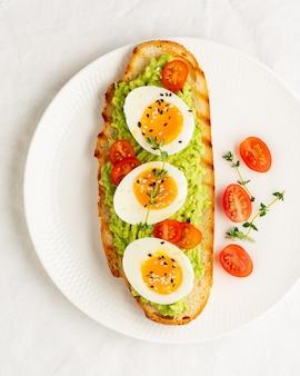 Toast di avocado con pane tostato, uova alla coque con pomodori