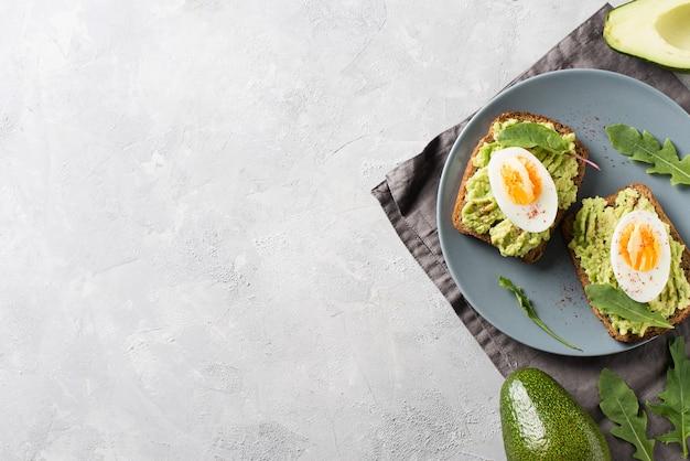 Avocado toast con uova e insalata a colazione, cibo pulito