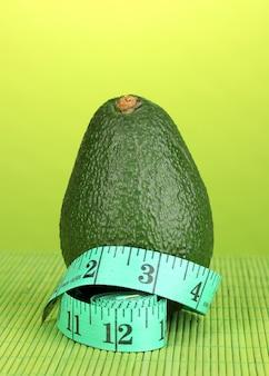 Avocado con nastro di misurazione sulla superficie verde
