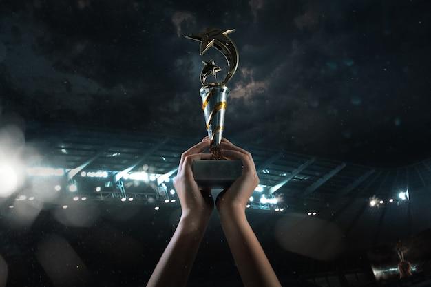 Premio della vittoria, mani maschili che stringono la coppa dei vincitori contro il cielo nuvoloso scuro