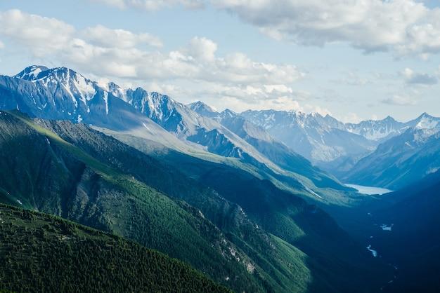 Splendida vista aerea del ghiacciaio delle grandi montagne e della valle della foresta verde con lago alpino