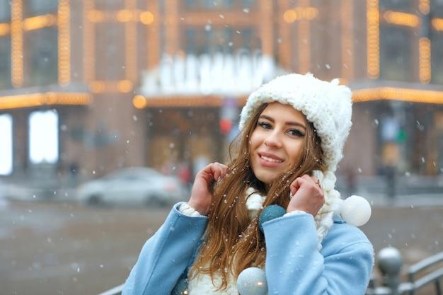 La fantastica donna bruna indossa un berretto e un cappotto a maglia che camminano per la città decorata con ghirlande. spazio per il testo