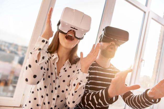 Dispositivo fantastico. basso angolo di energica coppia positiva attraente che indossa cuffie vr e muove le mani mentre apre la bocca