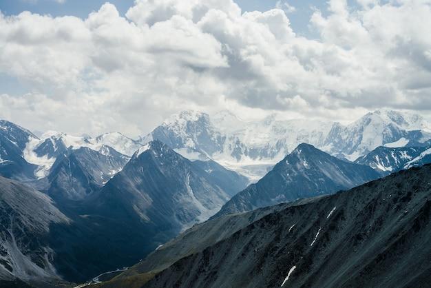 Incredibile paesaggio alpino drammatico con bellissime enormi montagne glaciali sotto il cielo nuvoloso grigio.