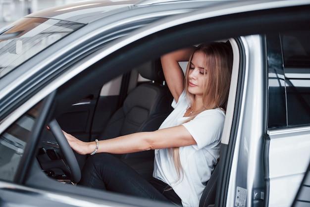 Sensazione fantastica. ragazza in macchina moderna nel salone. di giorno al chiuso. acquisto di un nuovo veicolo