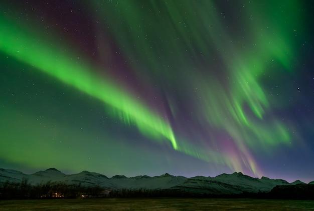 Awesome aurora verde e viola sulle montagne coperte di neve, islanda.
