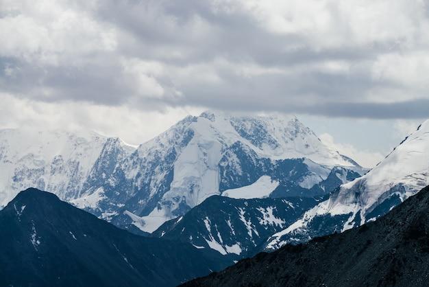 Fantastico paesaggio con enormi montagne glaciali in cattivo tempo nuvoloso.