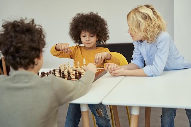 Fantastico ragazzino con i capelli afro che sembra concentrato mentre gioca a scacchi nella stanza con altri