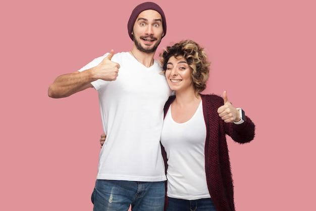 Stupendo. ritratto di coppia positiva di amici in stile casual in piedi, abbracciando e mostrando i pollici con un sorriso a trentadue denti, guardando la fotocamera. isolato, interno, girato in studio, sfondo rosa