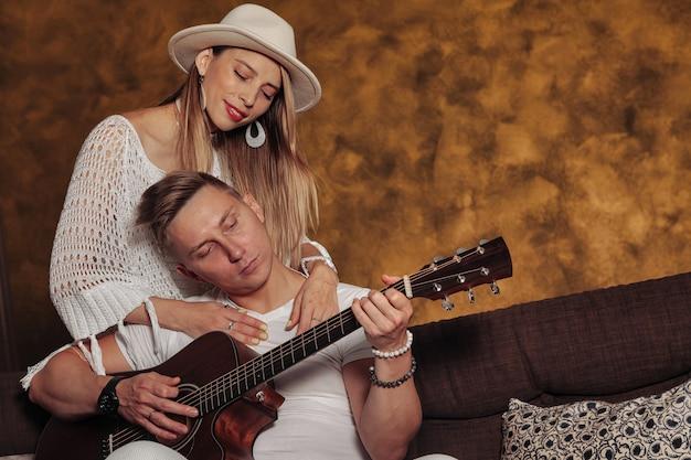 Fantastico giovane e donna in abiti bianchi con la chitarra all'interno del soggiorno. coppia sul divano con la chitarra. concetto di apprendimento a casa o musica a casa e educazione musicale. copia spazio