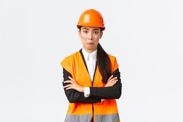 Ingegnere femminile asiatico imbarazzante in giacca riflettente, casco di sicurezza, petto a braccia incrociate e sorrisetto sorpreso, commettendo uno stupido errore, comportandosi in modo naturale, in piedi sfondo bianco