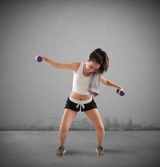 Ragazza imbarazzante che cerca di sollevare pesi durante l'allenamento