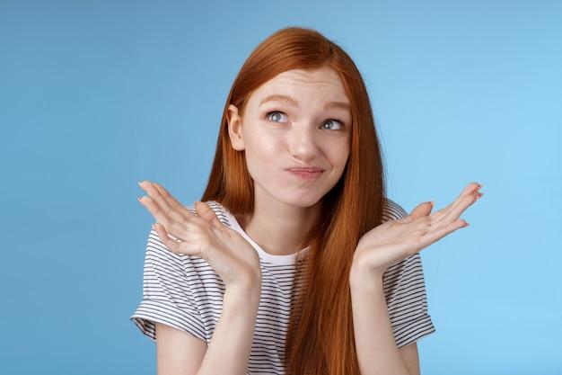 Ragazza popolare rossa attraente scomoda scomoda che prova a pensare a scusa sentirsi riluttante in piedi incerto alzando le spalle dubbioso diffondere le mani lateralmente sorridendo guardare in alto esitante.