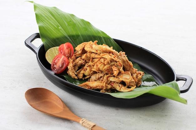 Ayam sisit o ayam suwir è una cucina balinese a base di pezzi piccanti di carne di pollo, serviti su piastra nera. copia spazio per il testo