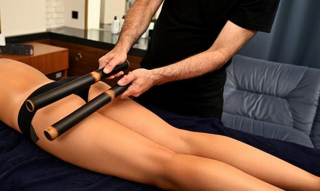 Massaggio ayurvedico con bastoncini di bambù eseguito da massaggiatore professionista sul corpo di una donna in una località termale