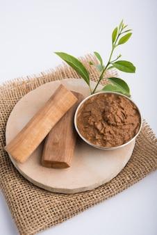 Chandan ayurvedico o pasta di legno di sandalo in una ciotola d'argento con foglie di bastoncini e foglie poste sopra sahanor sahana o base circolare in pietra per creare pasta