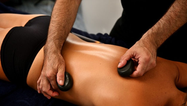 Massaggio ayurvedico con pietre calde nel moderno salone spa. concetto di cura del corpo. massaggiatore che massaggia la schiena della donna con pietre laviche