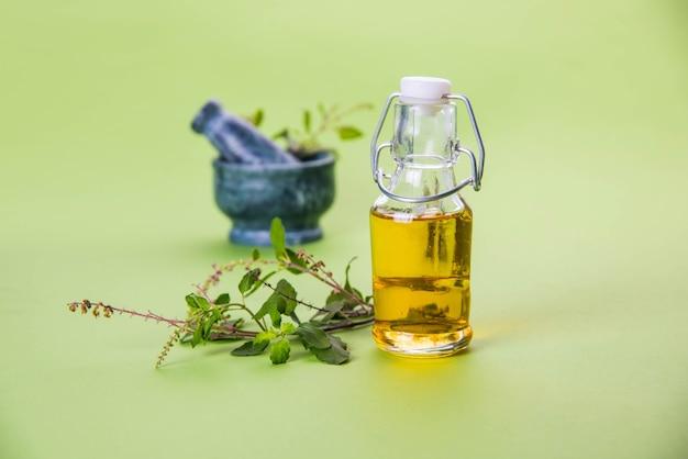 Olio ayurvedico di tulsi, estratto di erbe regina in bottiglia di vetro con rami di basilico santo verde fresco e mortaio con pestello. isolato su sfondo colorato. messa a fuoco selettiva