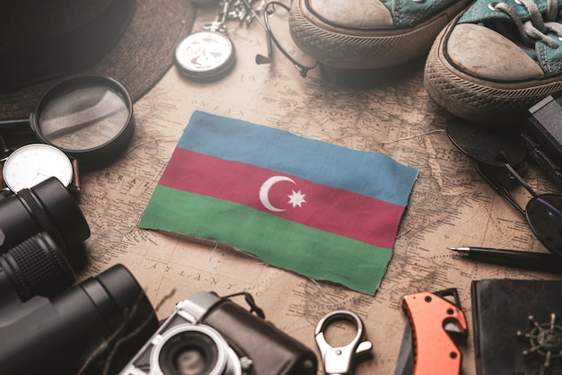 Bandiera dell'azerbaijan tra gli accessori del viaggiatore sulla vecchia mappa d'annata. concetto di destinazione turistica.