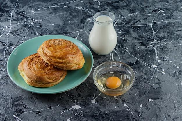 Pasticceria nazionale dell'azerbaigian con uovo di gallina crudo e una brocca di vetro di latte fresco