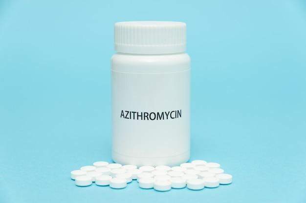 Antibiotico azitromicina in confezione di bottiglia bianca con pillole sparse su sfondo azzurro