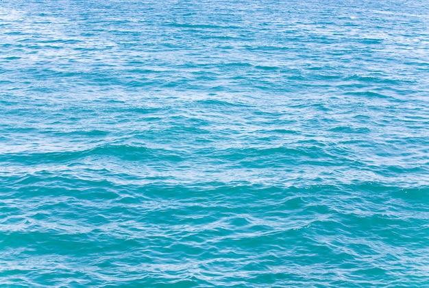 Superficie dell'acqua di mare azzurra con ripple e riflessi di nuvole