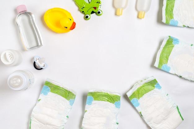 Prodotti per neonati pannolini per bambini in polvere crema shampoo olio su sfondo bianco con copia spazio vista dall'alto o fl...