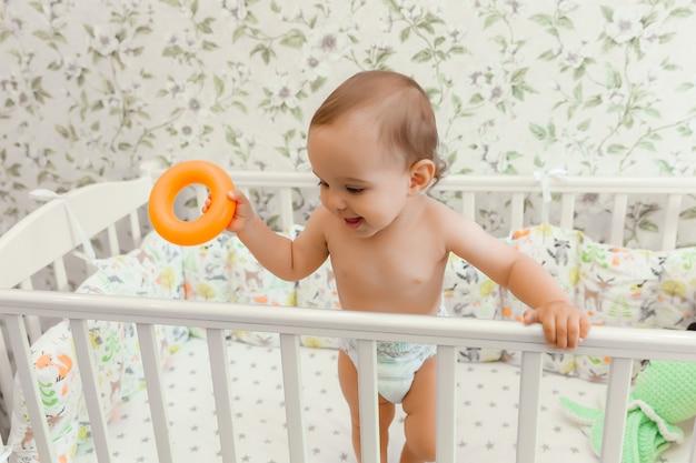 Un bambino di 11 mesi in un pannolino sta nella sua culla bambino nel letto
