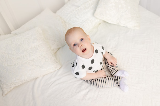 Bambino di 8 mesi seduto sul letto a casa in pigiama e guardando la telecamera, vista dall'alto, posto per il testo
