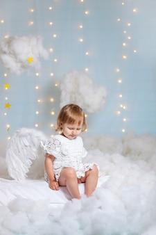 Angelo bambino seduto tra le nuvole guardando verso il basso