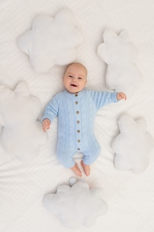 Bambino sul letto tra i cuscini delle nuvole. tessili e biancheria da letto per bambini.
