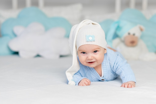 Un bambino su un letto in un cappuccio va a letto o si sveglia al mattino. tessili e biancheria da letto per bambini. neonato con un orsetto giocattolo