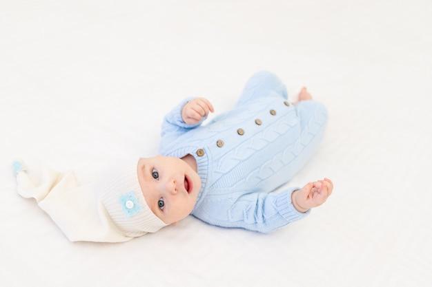 Bambino sul letto in un berretto per dormire. tessili e biancheria da letto per bambini. la mattina del bambino