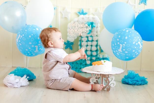 Bambino 1 anno in uno studio fotografico con una torta e palloncini, compleanno di un bambino 1 anno, il bambino mangia la torta