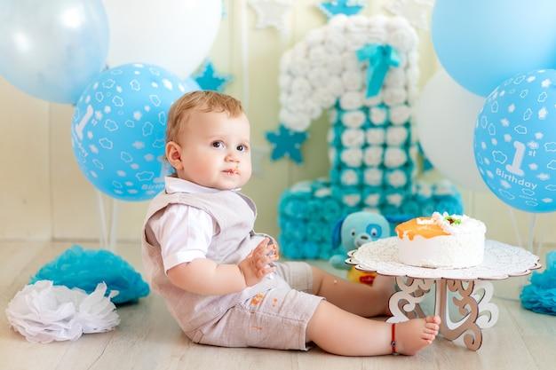 Neonato 1 anno con una torta e palloncini, compleanno di un bambino di 1 anno, il bambino mangia la torta