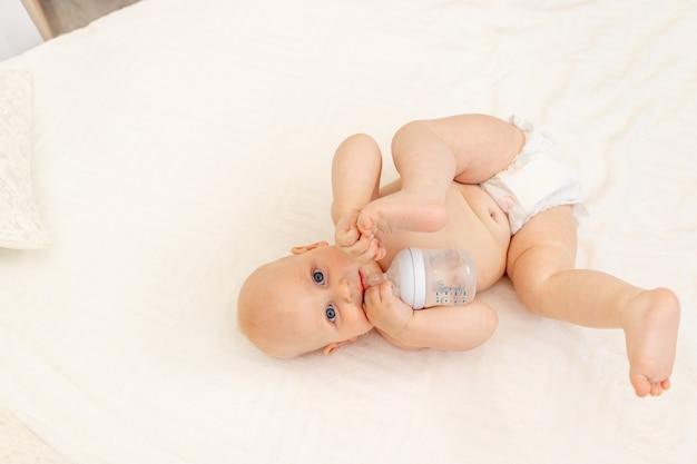 Baby boy 8 mesi giacente in pannolini su un letto bianco con una bottiglia di latte a casa gambe in alto, vista dall'alto, concetto di pappe, acqua potabile del bambino da una bottiglia