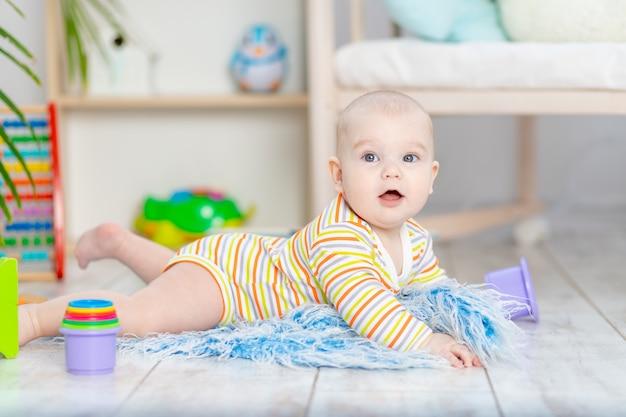 Neonato tra i giocattoli nella stanza dei bambini, piccolo bambino sorridente divertente sveglio che gioca sul pavimento, il concetto di sviluppo e giochi dei bambini