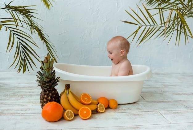 Il neonato si bagna in un bagno di latte con frutta su una superficie bianca con spazio per il testo