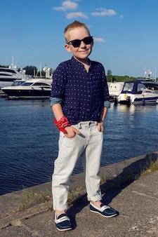 Neonato biondo 8 anni in una camicia blu, pantaloni leggeri e occhiali da sole che cammina sul lungomare in riva al mare con yacht ormeggiati vicino alla riva in estate con tempo soleggiato