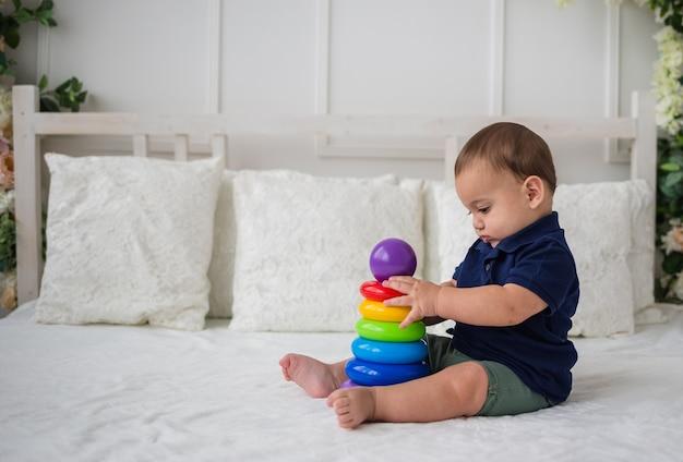 Un neonato con una maglietta blu e pantaloncini beige si siede su un letto bianco e gioca con un giocattolo piramidale