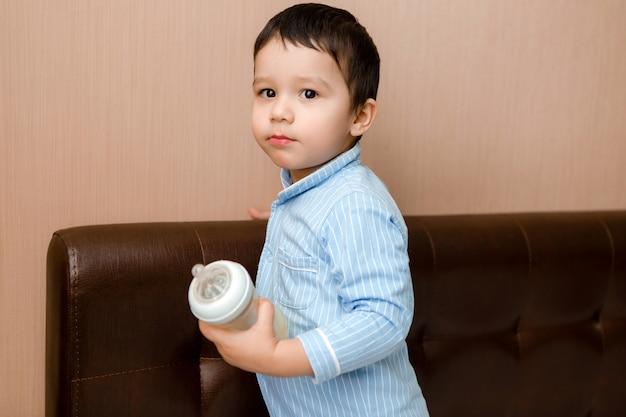 Il neonato del brunette si trova sul letto in pigiama blu e beve il latte da una bottiglia. cibo per bambini