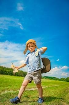 Un bambino in aereo gioca sulla natura nel parco. ragazzo in vacanza pilota.