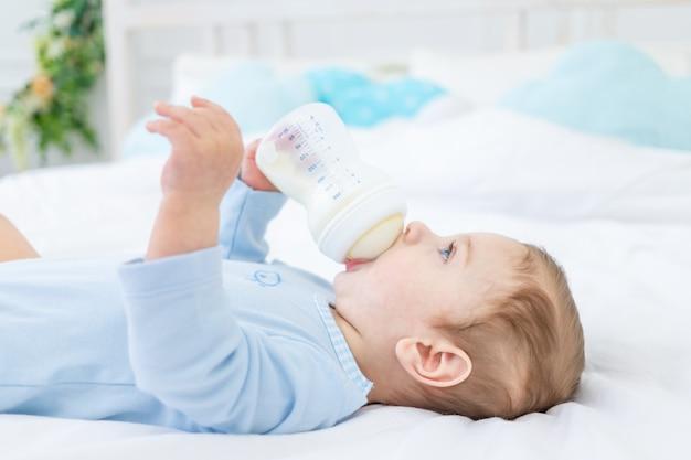 Il bambino c mangia il latte da una bottiglia sul letto prima di andare a letto in una tuta blu, concetto di alimenti per bambini