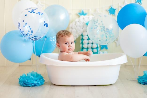 Bambino festeggia il compleanno 1 anno in una vasca da bagno con palloncini, bagnando il bambino con palloncini blu