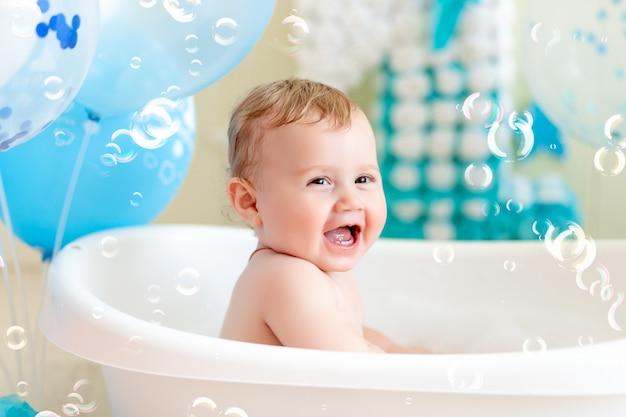 Il bambino festeggia il compleanno di 1 anno in un bagno con palloncini, facendo il bagno bambino con palloncini blu