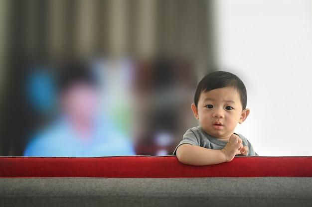 Neonato che si arrampica sul divano nel soggiorno di casa.