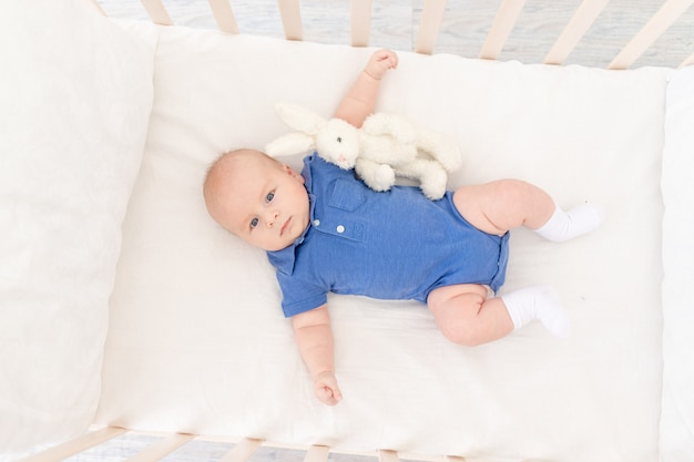 Il neonato in una culla giace sulla schiena con un giocattolo, un neonato felice si sveglia