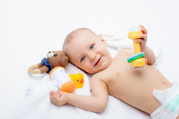 Un bambino in un pannolino con giocattoli giace su uno sfondo bianco isolato