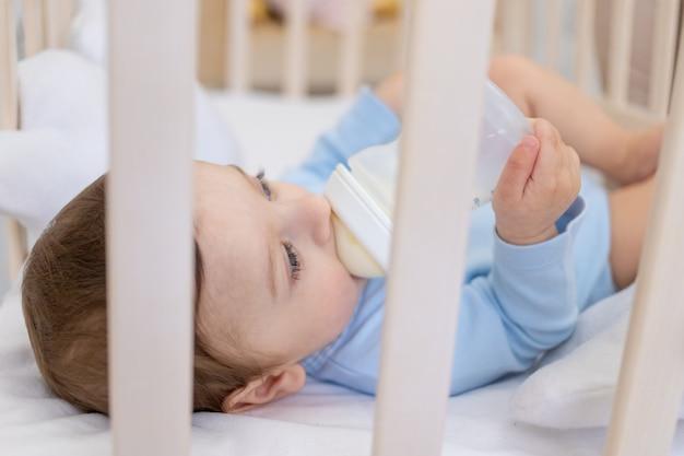 Neonato che mangia dalla bottiglia di latte nella culla in tuta blu, piccolo bambino carino in camera da letto, concetto di pappe