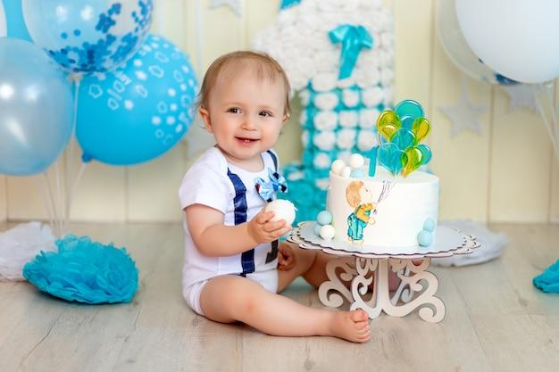 Neonato che mangia le sue mani di torta di compleanno